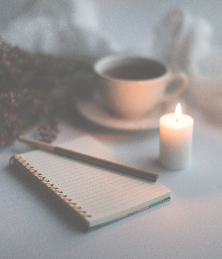 Photo by Sixteen Miles Out on Unsplash depicting a candle, notebook and cup of coffee on a table
